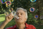 older man with respiratory disease blowing bubbles